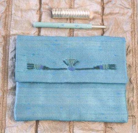 Для украшения этой шелковой вечерней сумочки был использован изящный узор из бисера в стиле ар-деко.